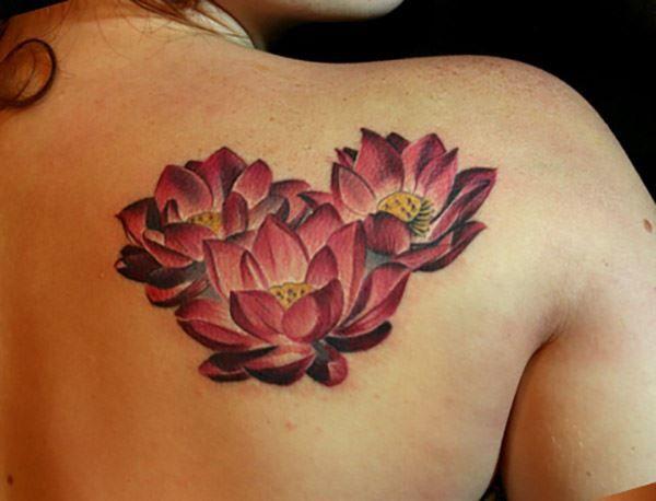 Тату лотоса для девушки на спине в цвете
