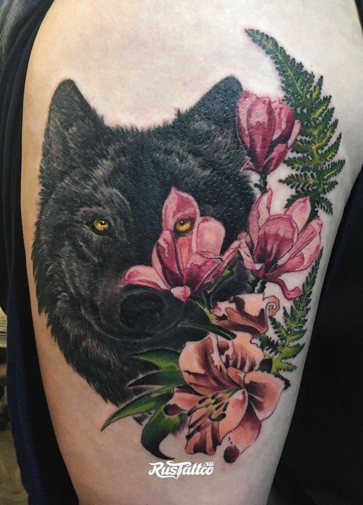 Тату черного волка с цветами на бедре