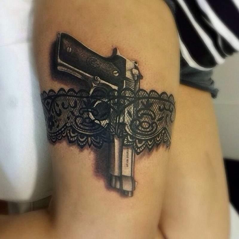 Тату кружева и пистолет в черном цвете на бедре