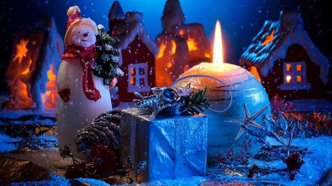 Снеговик с елочными игрушками и горящей свечой на фоне домов