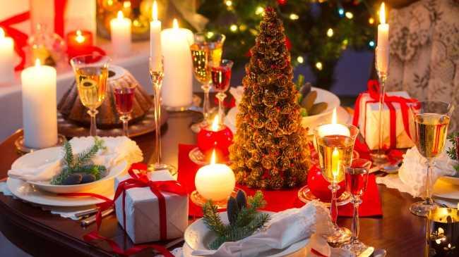 Обеденный праздничный новогодний стол со свечами, посудой, елкой