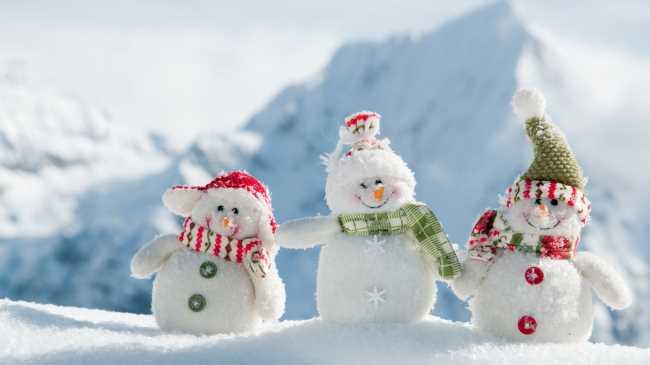 Три снеговика в горах в снегу