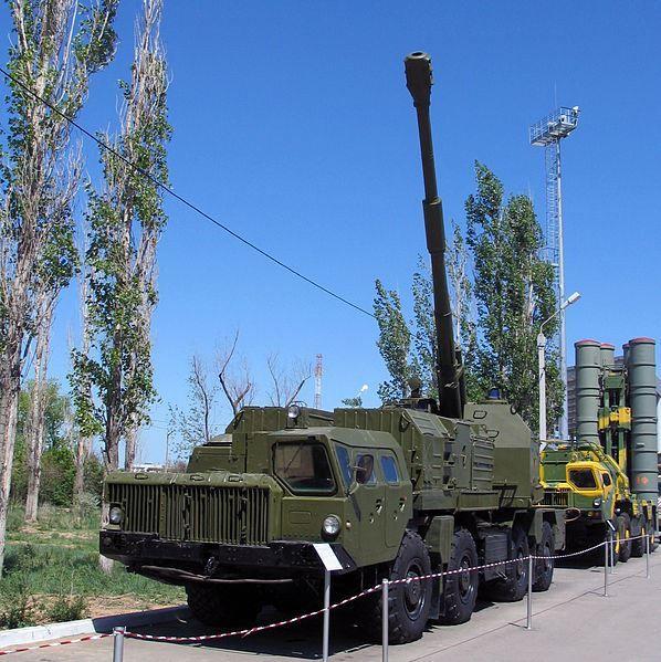 Самоходная артиллерийская установка берегового артиллерийского комплекса АК-222 Берег на колёсном шасси МАЗ-543М на выставке военной техники посвящённой 65-летию полигона Капустин Яр, город Знаменск. На заднем плане СПУ ЗРК С-300